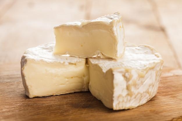 Seção de queijo camembert na placa de madeira. imagem macro