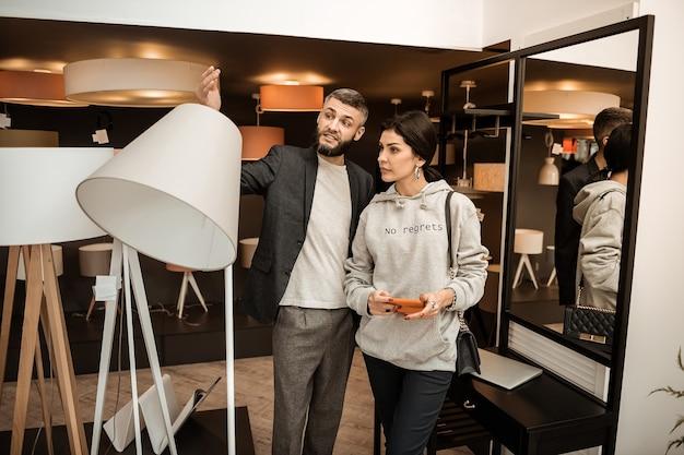 Seção de relâmpagos. homem barbudo de jaqueta preta gesticulando expressivamente durante a discussão enquanto sua esposa está por perto