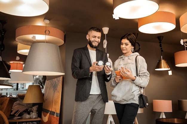 Seção de relâmpagos. homem barbudo sorridente carregando lâmpadas simples, enquanto sua esposa segurando um tablet e olhando com dúvidas