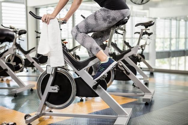 Seção inferior de ajuste mulher na bicicleta ergométrica no ginásio
