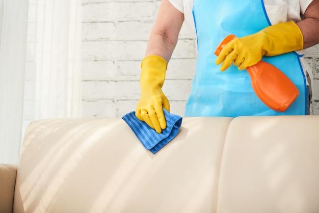 Seção intermediária da empregada irreconhecível, limpando o sofá de couro com spray de polimento de couro