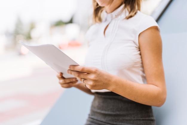Seção intermediária da empresária segurando documentos de papel branco no exterior