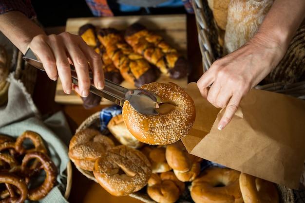 Seção intermediária da equipe embalando donut em saco de papel no balcão