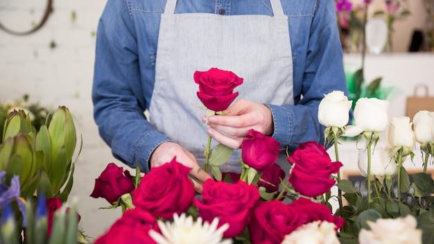 Seção intermediária da florista masculina organizando a flor rosa no buquê