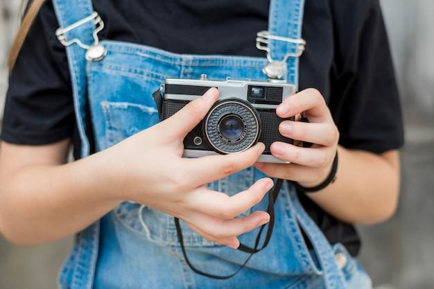 Seção intermediária da mão de garota, ajustando a lente da câmera retro