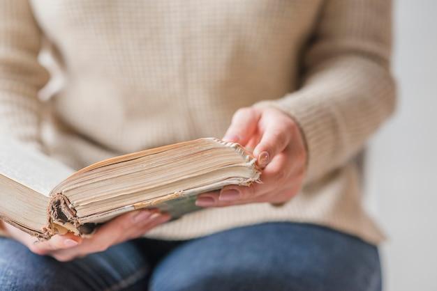 Seção intermediária da mão de uma mulher segurando um livro antigo aberto