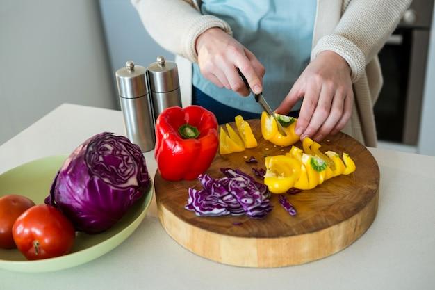 Seção intermediária da mulher cortando pimentão amarelo na cozinha