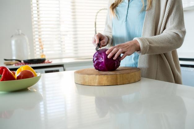 Seção intermediária da mulher cortando repolho roxo na cozinha