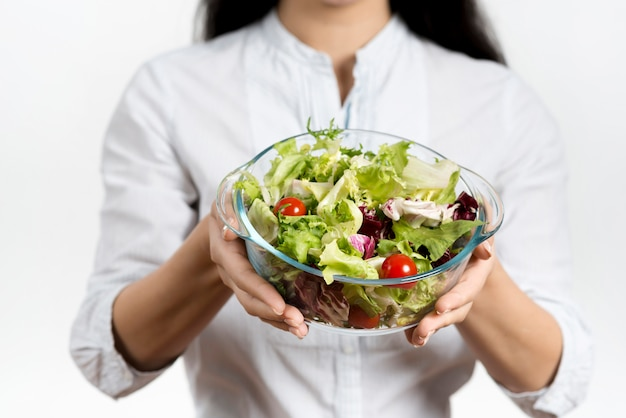 Seção intermediária da mulher segurando a tigela de salada vegetariana saudável