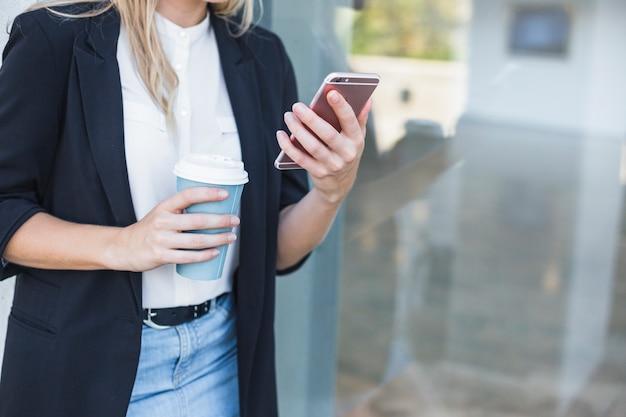Seção intermediária da mulher segurando o copo de café de eliminação segurando o smartphone
