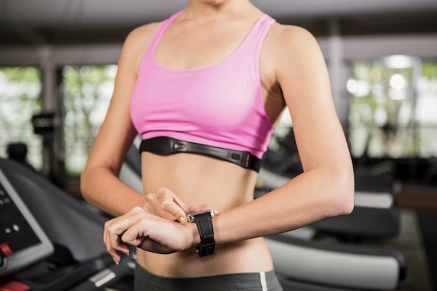 Seção intermediária da mulher usando relógio inteligente na esteira