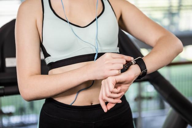 Seção intermediária da mulher usando smartwatch no ginásio