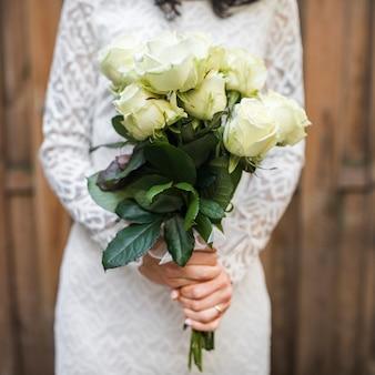 Seção intermediária da noiva segurando o buquê de rosas