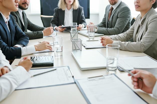 Seção intermediária de corretores interculturais contemporâneos ou parceiros de negócios sentados à mesa na sala de reuniões e discutindo estratégias