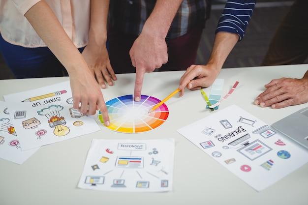 Seção intermediária de designers gráficos interagindo entre si enquanto trabalham