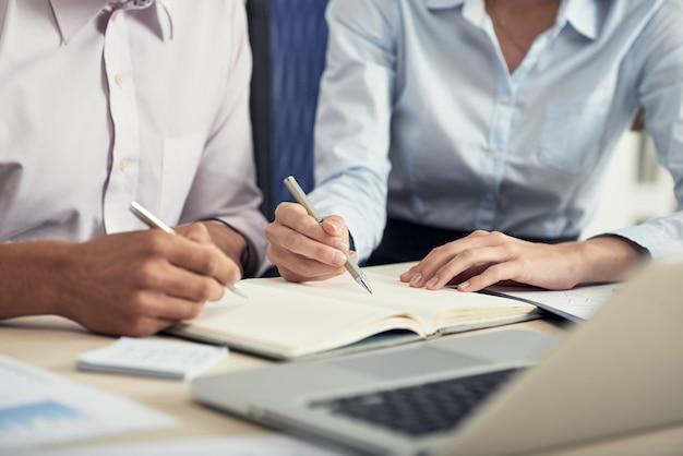 Seção intermediária de dois colegas fazendo brainstorming e fazendo anotações