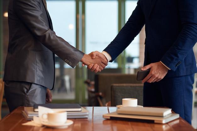 Seção intermediária de dois empresários irreconhecíveis, apertando as mãos para finalizar o acordo