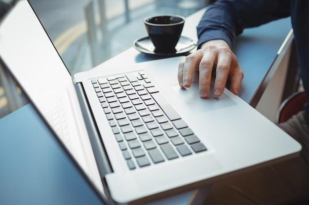 Seção intermediária de executivo masculino usando laptop