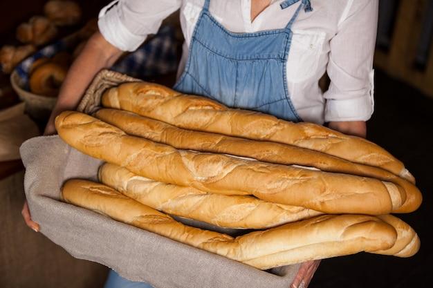 Seção intermediária de funcionárias segurando cesta de baguetes na seção de padaria