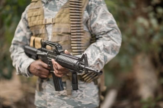 Seção intermediária de soldado militar segurando um rifle no campo de treinamento