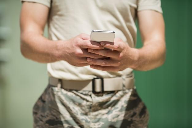 Seção intermediária de soldado militar usando telefone celular no campo de treinamento