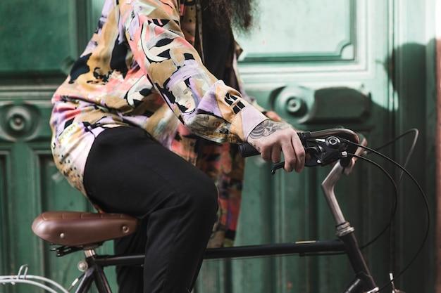 Seção intermediária de um homem sentado na bicicleta