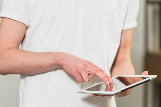 Seção intermediária de um homem tocando a tela do tablet digital com os dedos