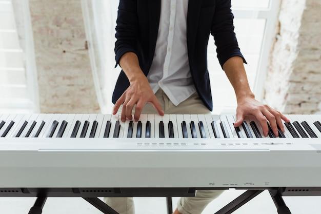 Seção intermediária de um jovem tocando o teclado de piano de cauda