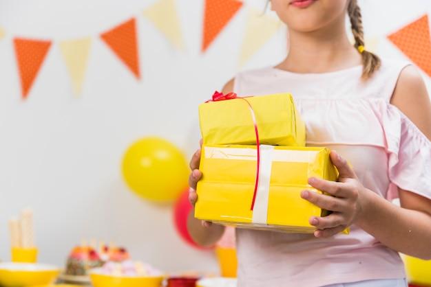 Seção intermediária de uma menina segurando caixas de presente na mão dela
