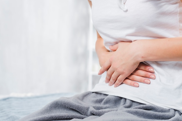 Seção intermediária de uma mulher com dor no abdômen