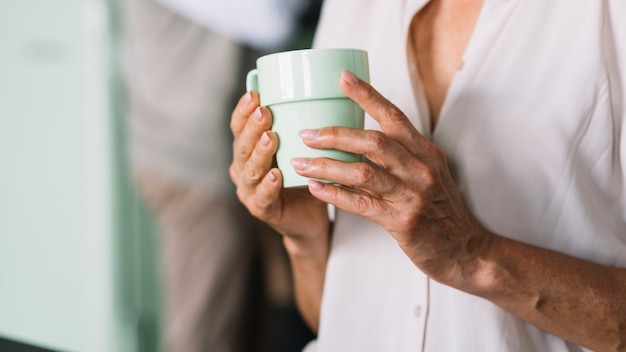 Seção intermediária de uma mulher idosa segurando a xícara de café