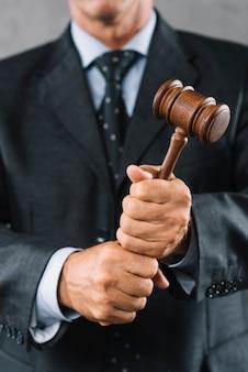 Seção intermediária do advogado masculino segurando o martelo de madeira na mão
