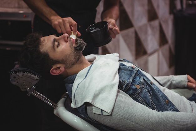 Seção intermediária do barbeiro aplicando creme na barba do cliente