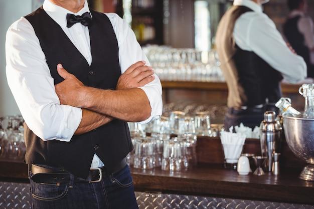 Seção intermediária do barman em pé com os braços cruzados