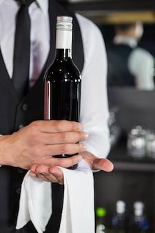 Seção intermediária do barman segurando uma garrafa de vinho em bar