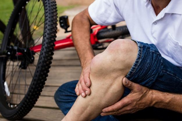 Seção intermediária do ciclista caído segurando o joelho machucado