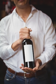 Seção intermediária do concurso de bar segurando uma garrafa de vinho