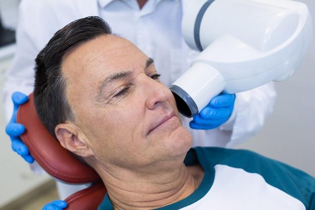 Seção intermediária do dentista examinando um paciente do sexo masculino com ferramenta odontológica