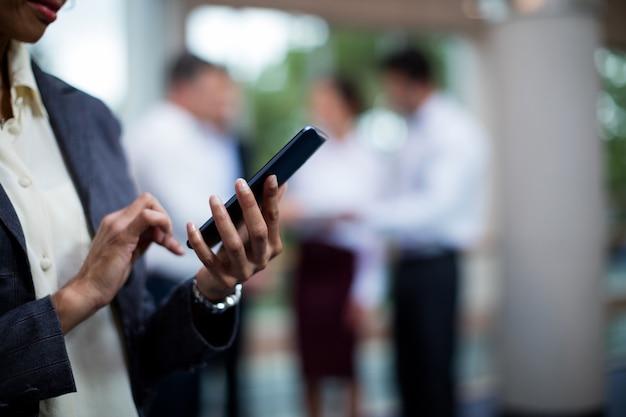 Seção intermediária do executivo de negócios feminino usando telefone celular
