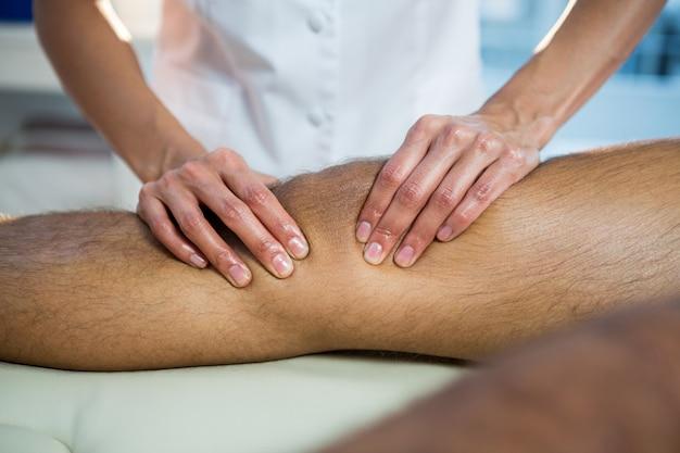 Seção intermediária do fisioterapeuta dando massagem nas pernas para um paciente
