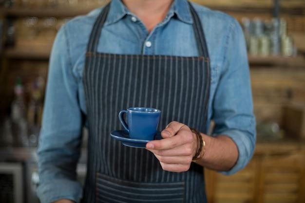 Seção intermediária do garçom servindo xícara de café