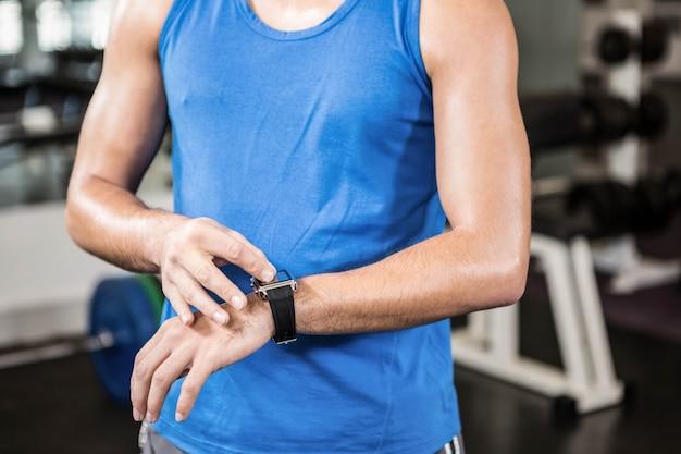 Seção intermediária do homem bonito usando smartwatch no ginásio