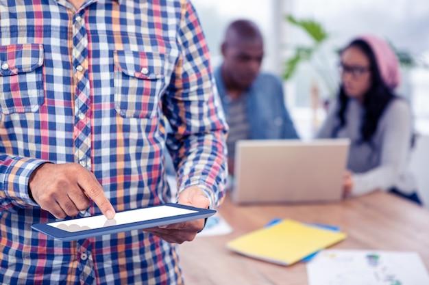 Seção intermediária do homem de negócios usando tablet digital no escritório criativo
