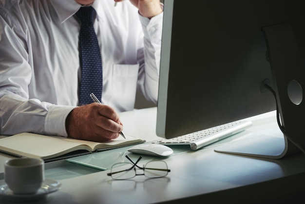 Seção intermediária do homem irreconhecível em trajes formais, fazendo anotações no computador no local de trabalho