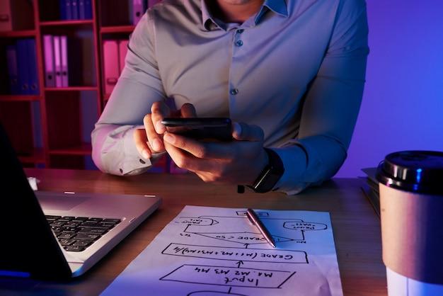 Seção intermediária do homem irreconhecível tirando foto do plano de trabalho no telefone
