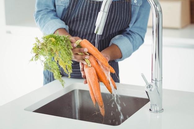 Seção intermediária do homem lavar as cenouras na cozinha