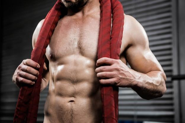 Seção intermediária do homem sem camisa com corda de batalha em volta do pescoço no ginásio crossfit