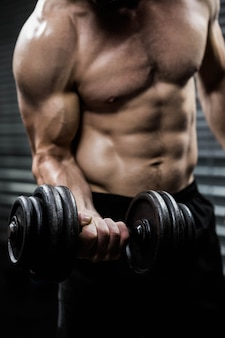 Seção intermediária do homem sem camisa, levantando halteres pesados no ginásio crossfit