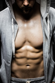 Seção intermediária do homem sem camisa usando o jumper no ginásio crossfit