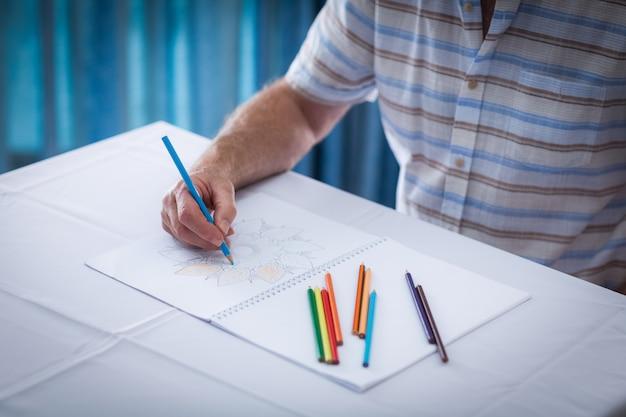 Seção intermediária do homem sênior, desenho no livro de desenho